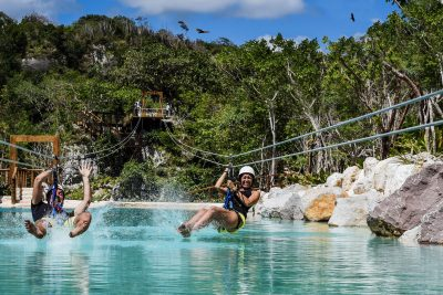 Two people zip lining over water